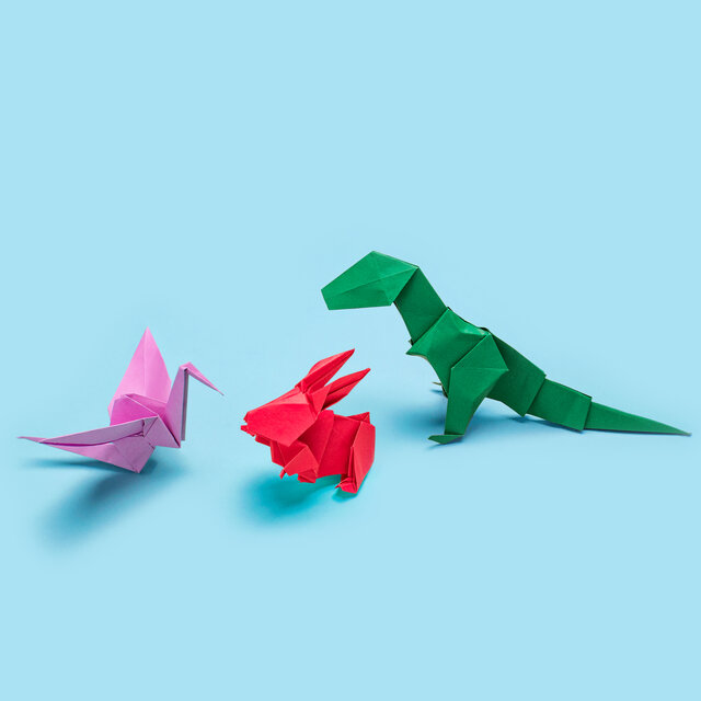 Origami of three dinosaurs on blue background