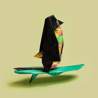 Origami penguin on a surfboard