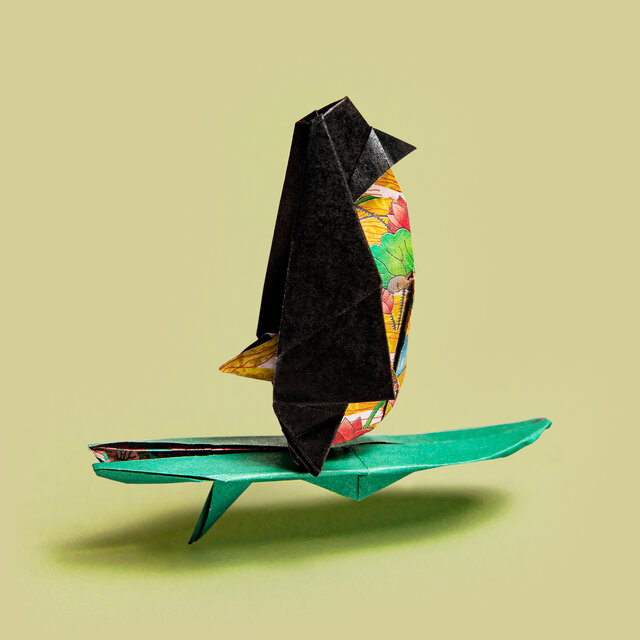Origami Pinguin auf einem Surfbrett