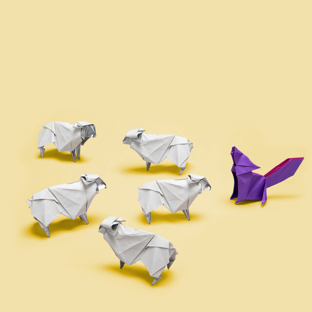 Origami of 5 sheep facing a wolf