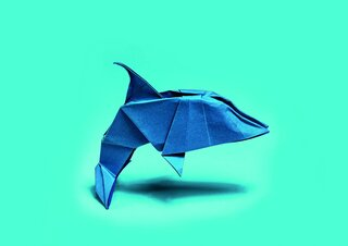 Blue origami dolphin on turquoise background